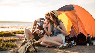 Casal na praia tocando violão e comendo Marshmallow