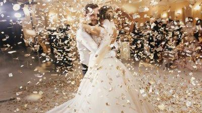 Homem e mulher com roupas de casamento sob uma chuva de confete.