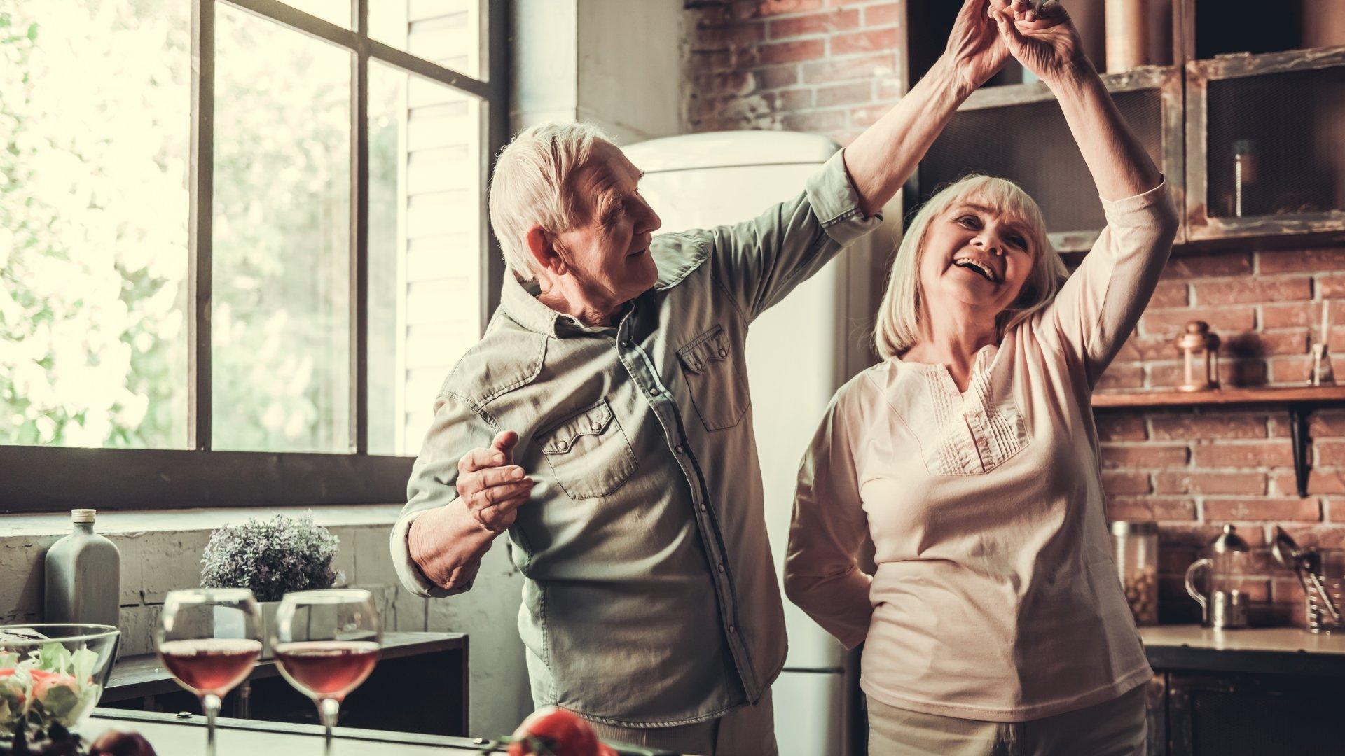 Casal de idosos felizes dançando na cozinha