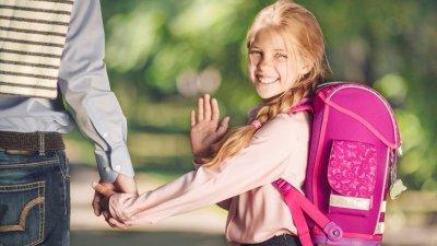 Menina com mochila nas costas dando tchau