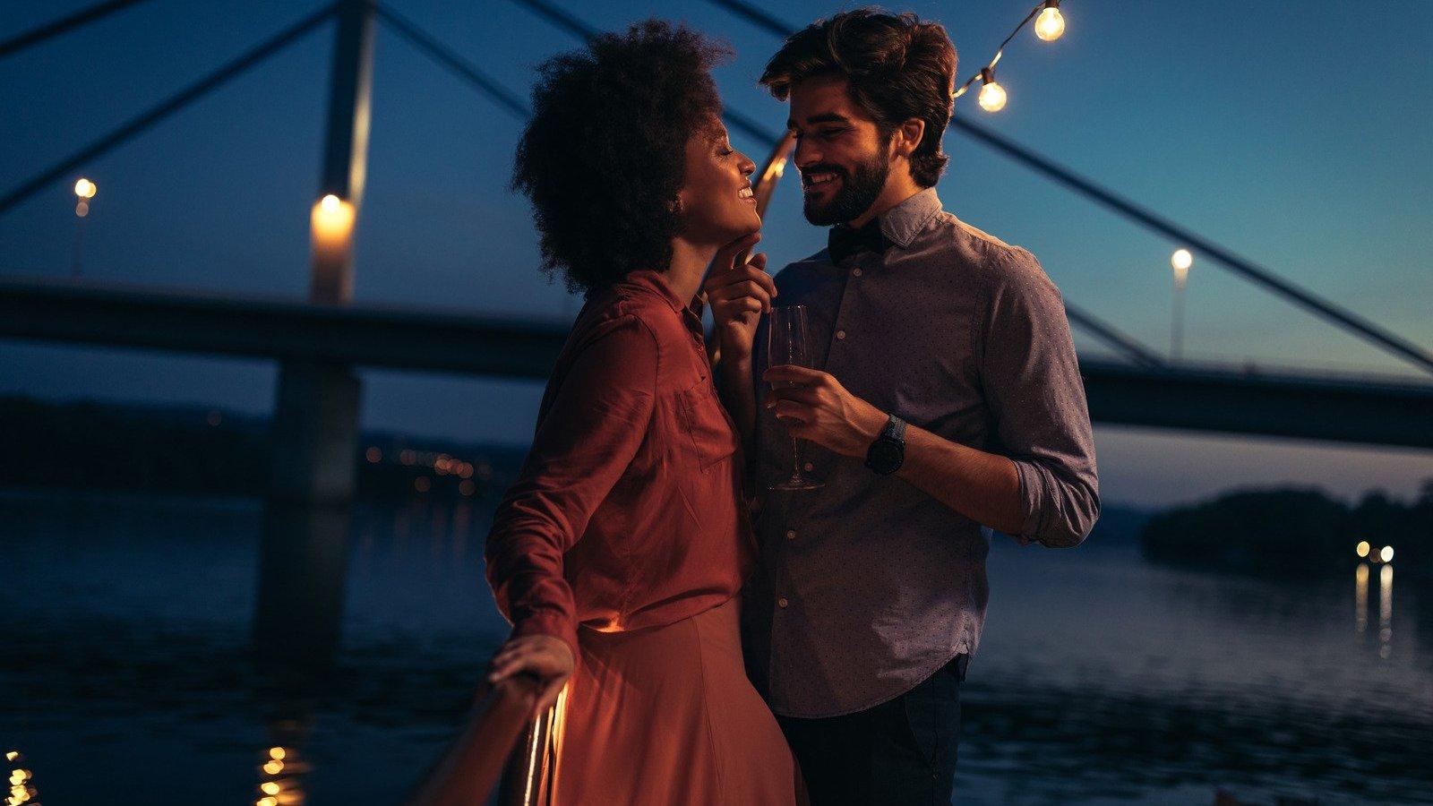 Homem branco e mulher negra abraçados num barco durante a noite.