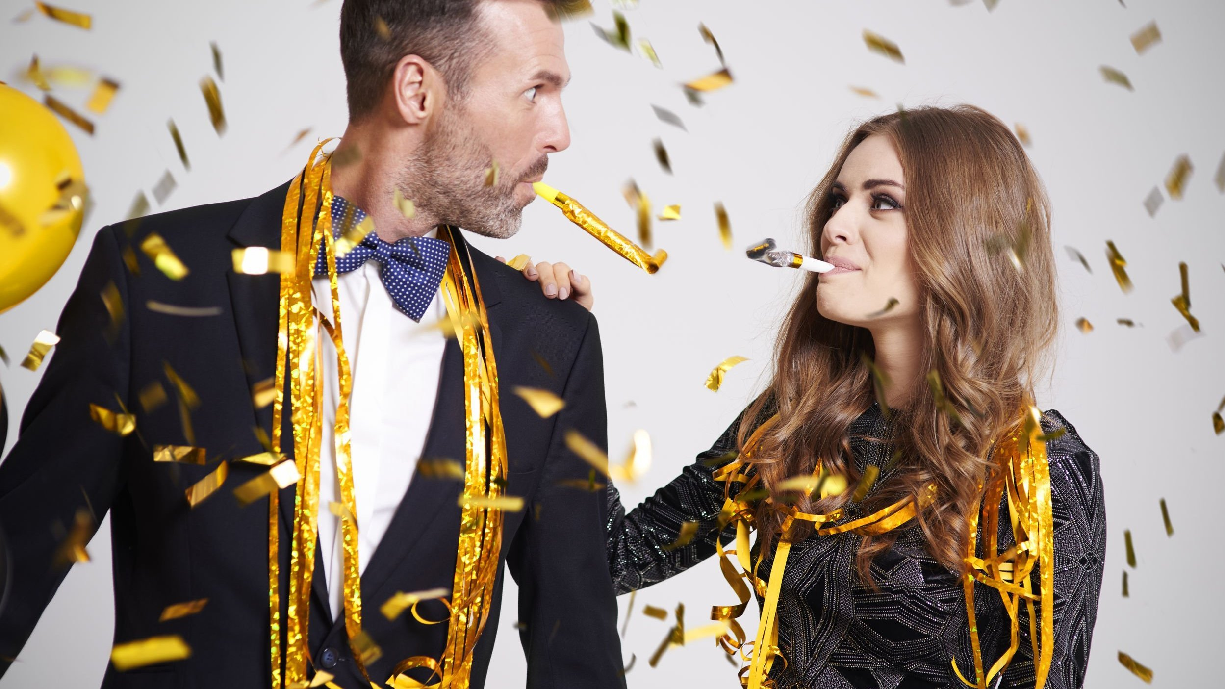 Homem e mulher com roupas de festa em meio a balões e confetes.