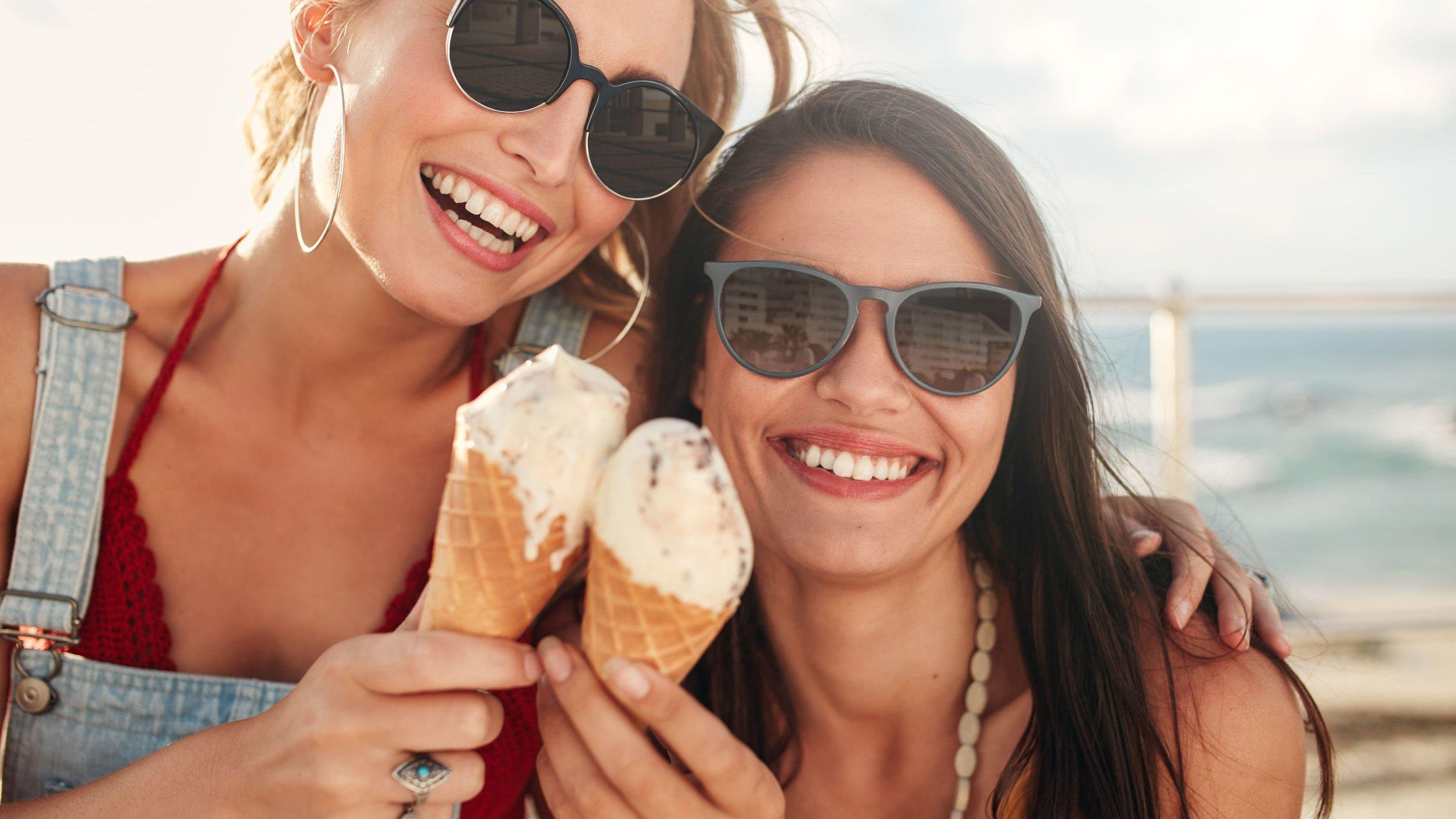Duas mulheres sorrindo em uma praia segurando sorvete de casquinha