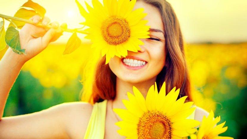 Garota sorrindo com girassóis em frente o rosto e sol refletindo