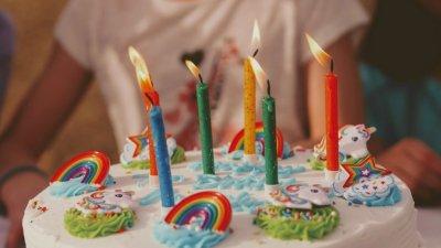 Bolo de aniversário de unicórnio com velas acesas.