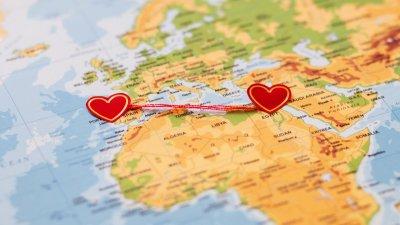 Um mapa da Europa e África, com dois corações em países diferentes. Esses corações são ligados por um fio vermelho.