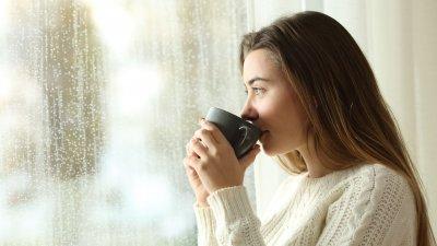 Mulher pensativa olhando pela janela enquanto toma uma bebida quente de uma caneca.