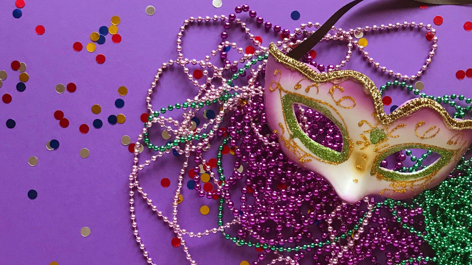 Máscara de carnaval no fundo roxo com confetes e colares coloridos de conta