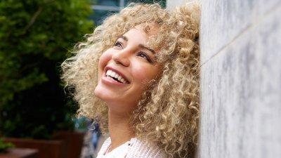 Mulher encostada em uma parede de concreto olhando para cima sorrindo
