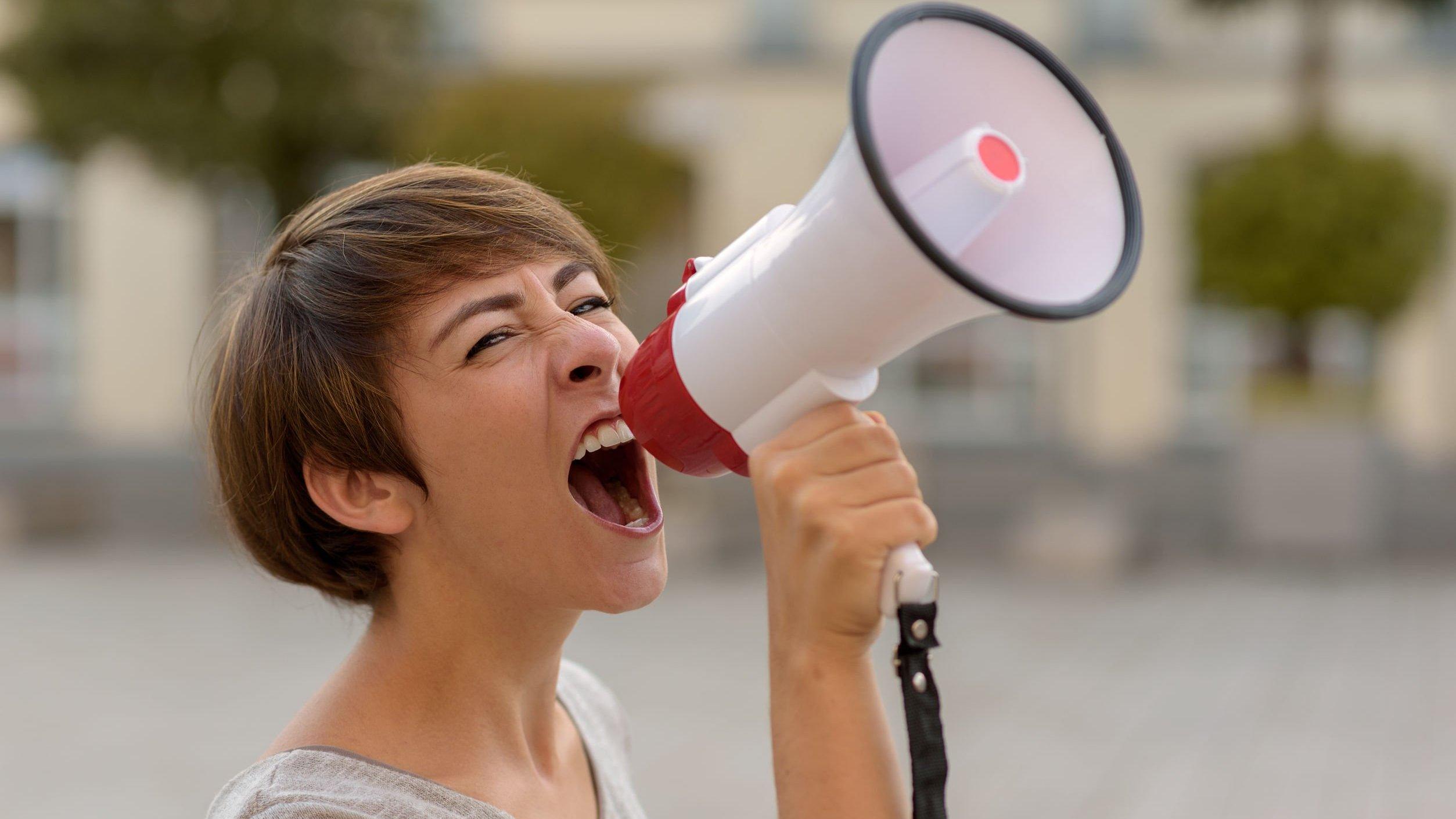 Mulher com megafone gritando em uma rua