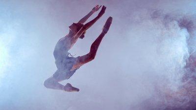 Bailarina dando um salto em meio à fumaça.