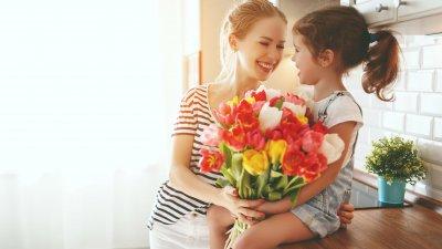 Mãe e filha brancas com buquê de flores nos braços e expressões felizes.