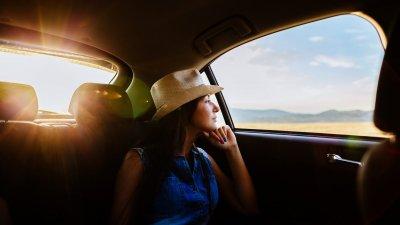 Mulher com chapéu e braços abertos