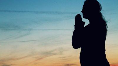 Silhueta de mulher rezando durante o pôr-do-sol.