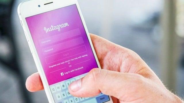 Mão segurando celular na página de login do Instagram