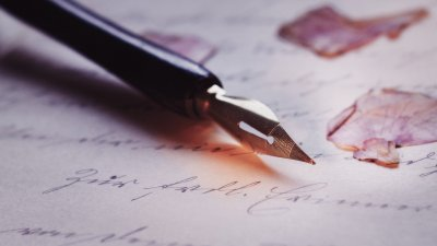 Caneta antiga em uma folha de papel com pétalas de flor