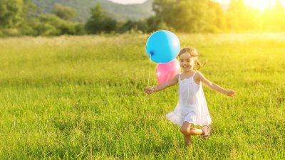 Menina pequena correndo em um campo enquanto segura balões de aniversário.