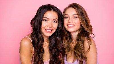 Duas mulheres lado a lado abraçadas sorrindo