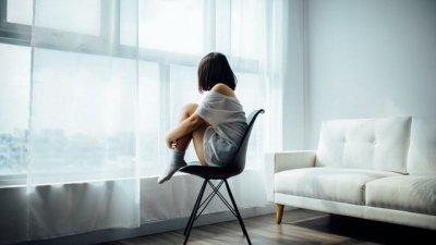 Mulher sentada em frente à janela com vista para o mar.