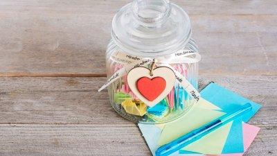 Pote de vidro transparente cheio de papéis coloridos dobrados. Um coração está amarrado na parte de fora do pote, e ao lado estão papéis coloridos e canetas.