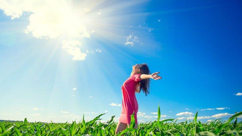 Mulher de braços abertos sendo iluminada pelo Sol