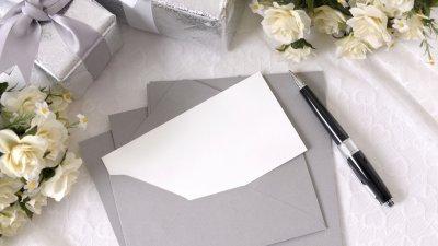 Envelopes com convites em branco em uma mesa, ao lado de flores e presentes.