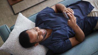 Homem deitado no sofá mexendo no celular sorrindo visto de cima