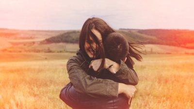 Homem e mulher abraçados em um campo de gramado