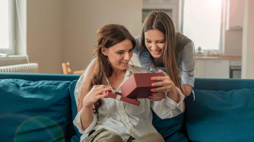 Mãe recebendo presente de filha e beijo no rosto
