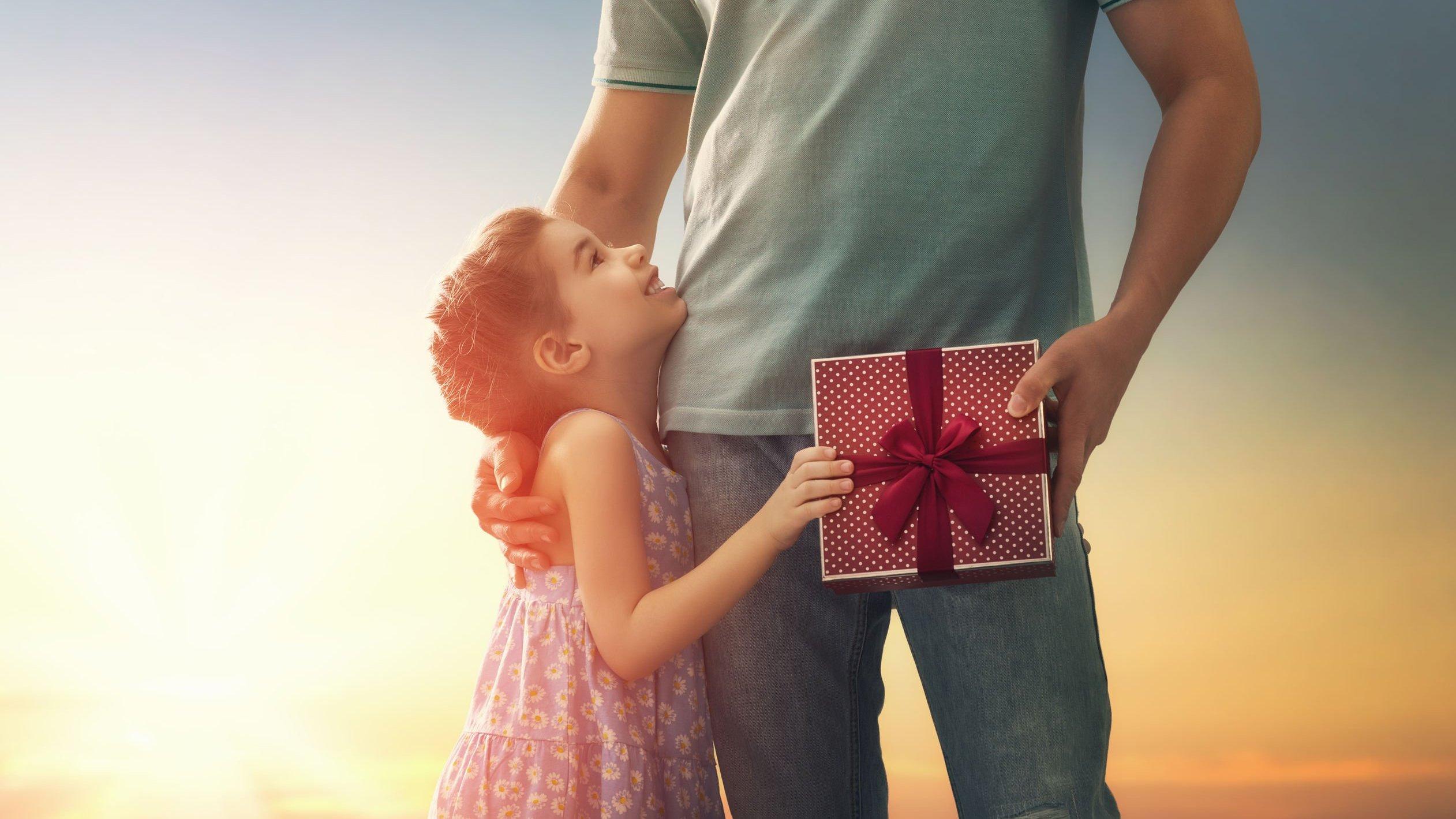Criança menina entregando um presente para o seu pai.