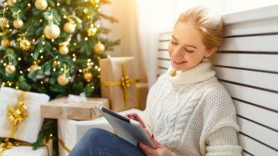 Mulher sentada olhando tablet com árvore de natal e presentes ao fundo