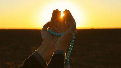 Mãos unidas segurando terço com sol refletindo ao fundo