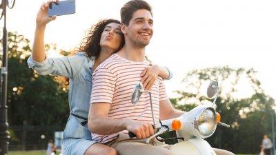 Casal em motocicleta tirando foto felizes