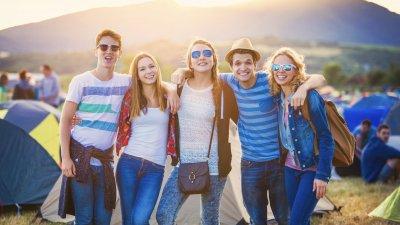 Grupo de amigos abraçados em acampamento