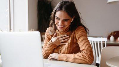 Mulher sorri e segura coração ao olhar para a tela de um computador