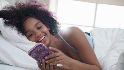 Homem e mulher um ao lado do outro com celular em mãos