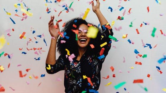Mulher comemorando com confetes coloridos