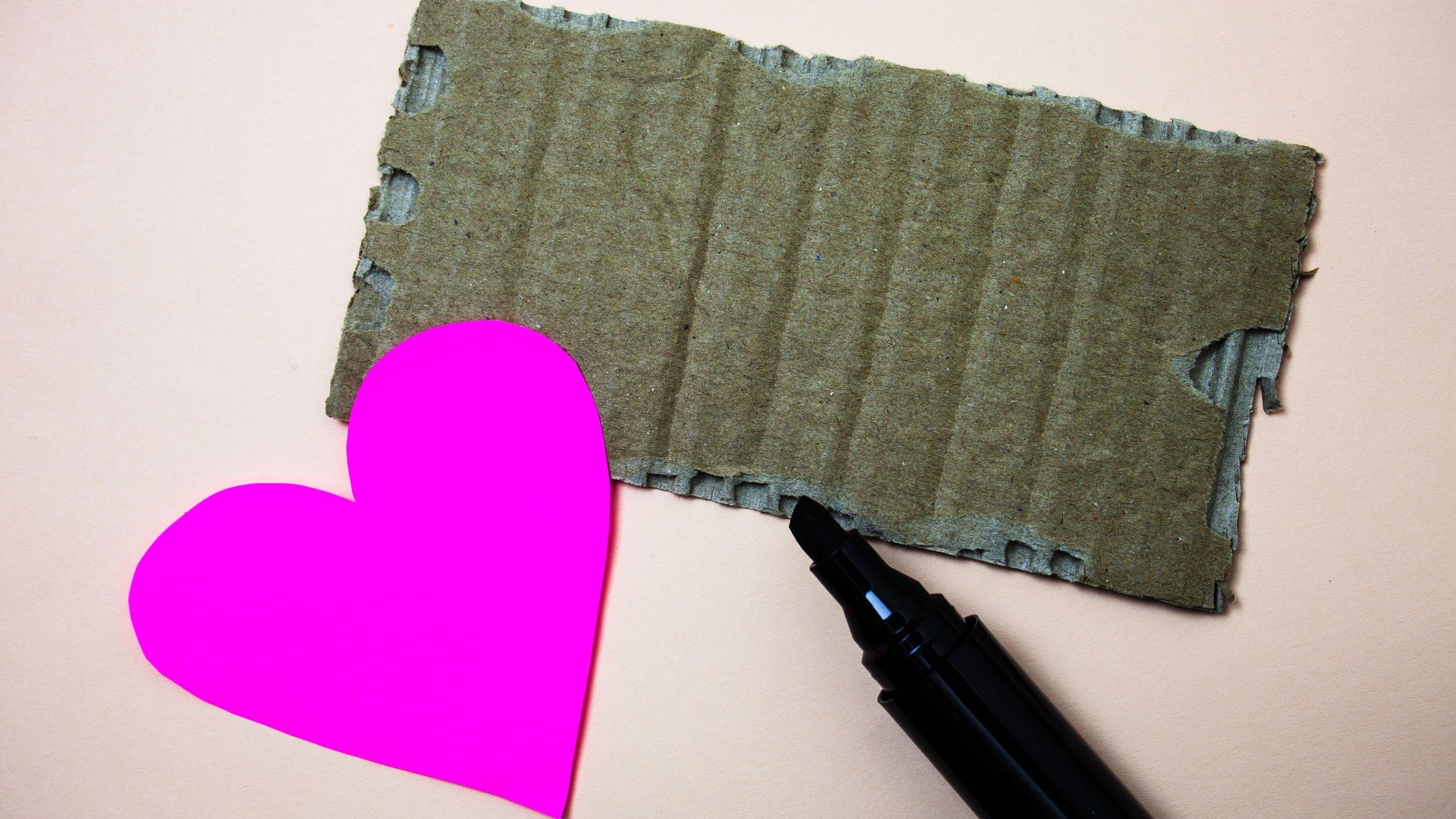 Coração de papel rosa ao lado de pedaço de papelão e canetinha preta