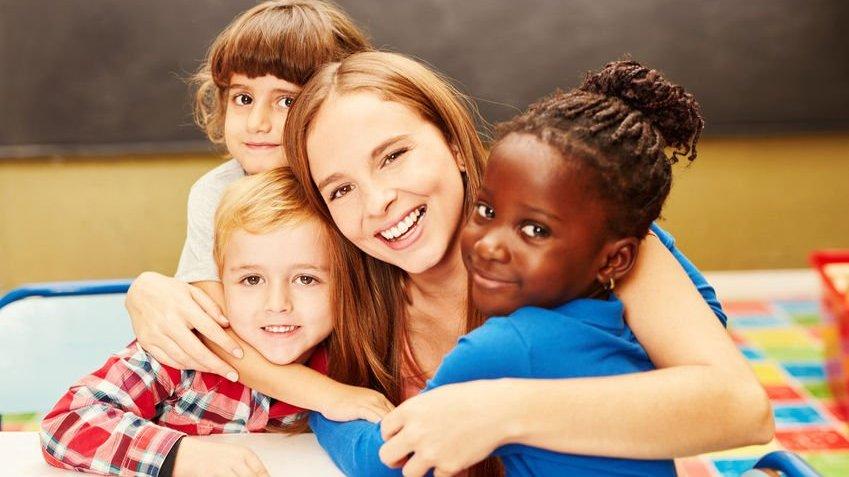 Crianças pequenas abraçando professora e sorrindo