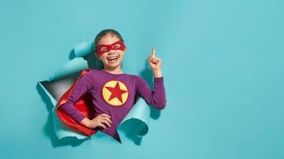 Criança sorrindo com fantasia de super-herói