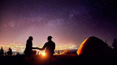Casal em volta de fogueira com barraca ao lado e céu estrelado com cidade ao fundo