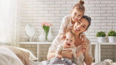 Mãe na cama com com filhos em seu colo