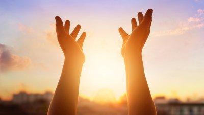 Mãos erguidas em direção ao céu ensolarado