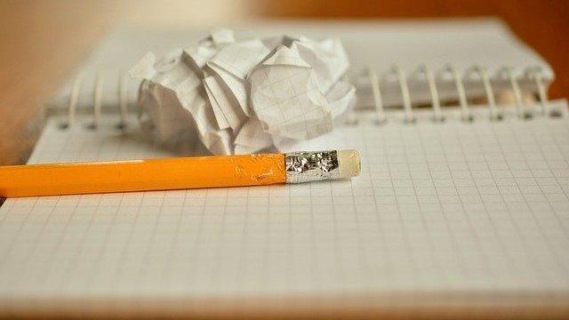 Lápis sobre caderno e folha amassada ao lado