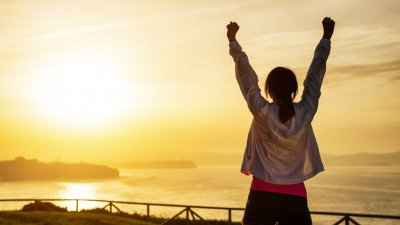 Mulher levantando os braços em direção ao mar e ao pôr do sol