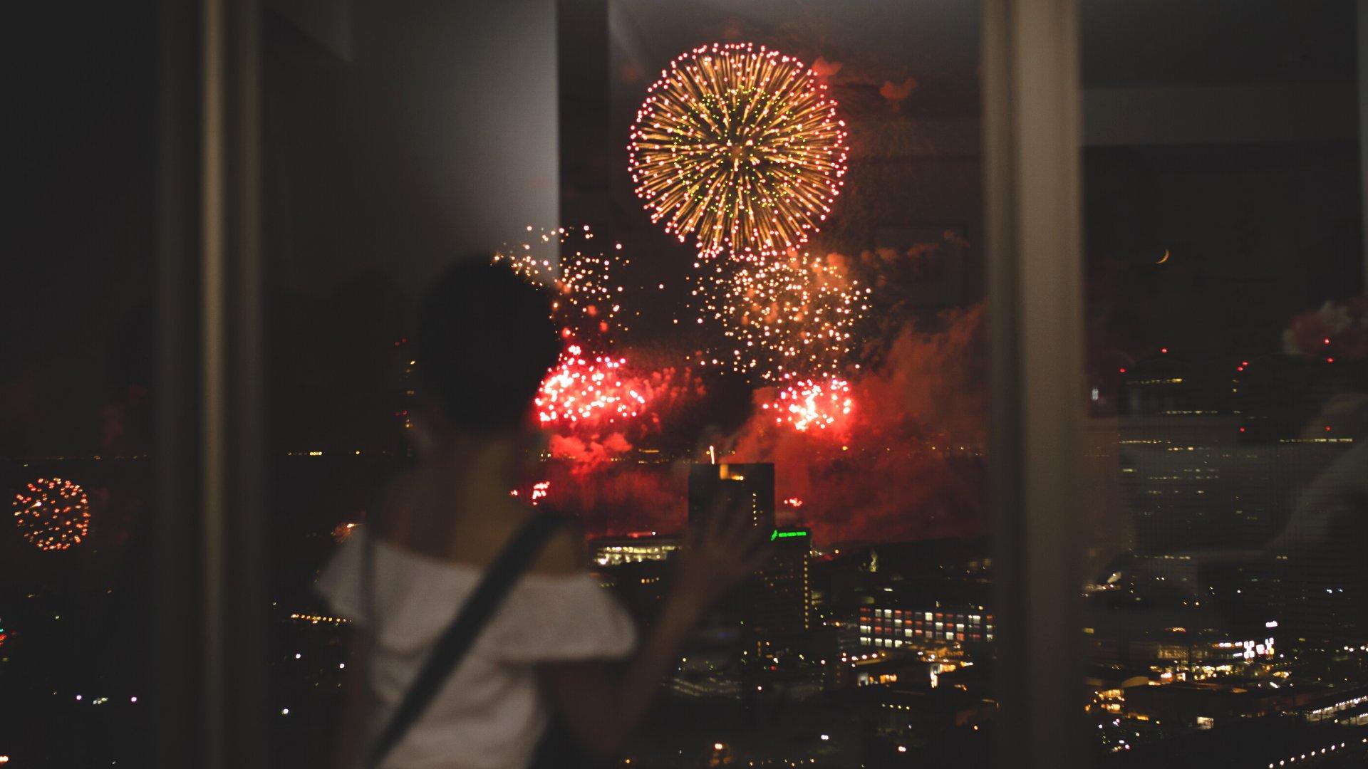 Mulher olhando os fogos de ano novo pela janela de um apartamento