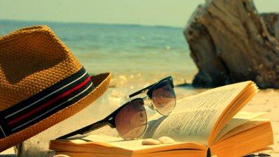 Paisagem de verão com praia, livros, óculos de sol e chapéu.