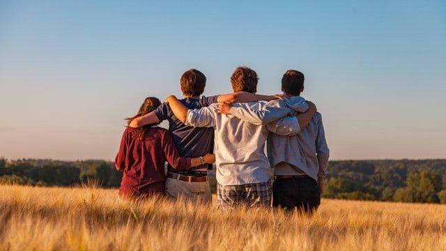 Quatro amigos de costas, abraçados, em um campo
