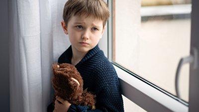 Criança triste olhando para o lado da janela, segurando ursinho de pelúcia