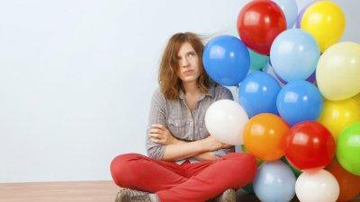 Mulher sentada no chão com expressão de tédio ao lado de balões coloridos.